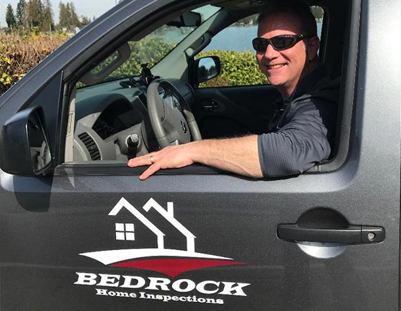 A photo of John Sexton in his truck with the Bedrock Home Inspections logo.